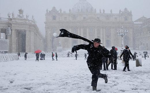 Молодой священник бросает снежок во время сильного снегопада на площади Святого Петра в Ватикане