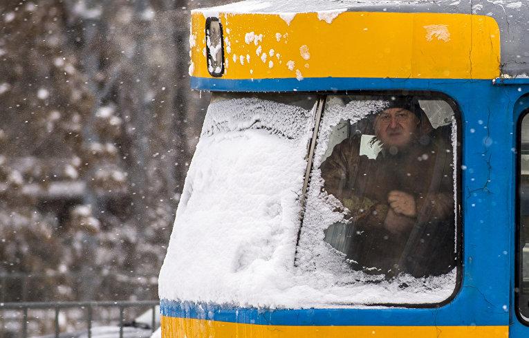 Мужчина смотрит в окно трамвая во время сильного снегопада в Софии, Болгария