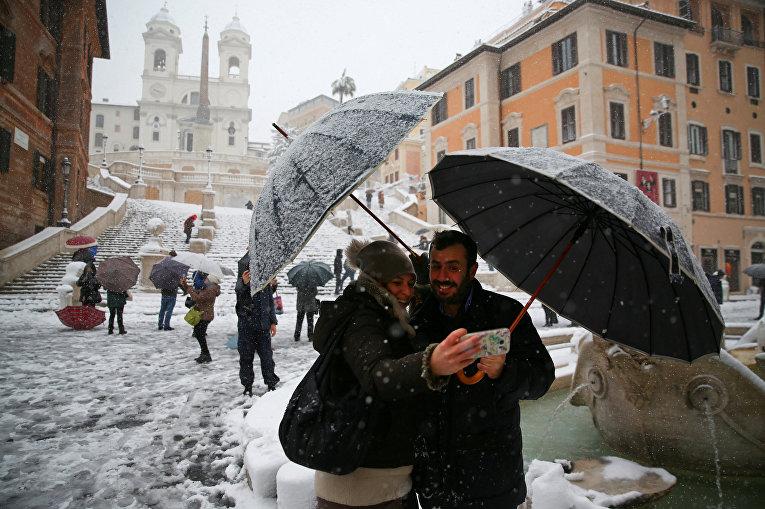 Пара перед заснеженным Колизеем во время снегопада в Риме, Италия