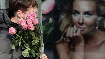 Мужчина с букетом цветов накануне праздника 8 марта в Москве