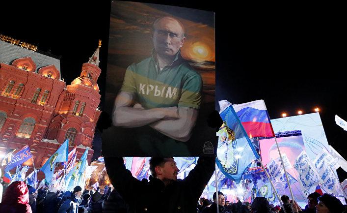 Мужчина держит плакат с изображением Владимира Путина