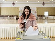 Девушка опускает бюллетень в урну на выборах президента РФ на избирательном участке в Бахчисарае. 18 марта 2018