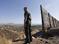 Сотрудник правоохранительных органов США у стены на границе США и Мексики в Сан-Диего
