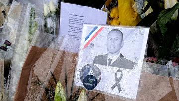 Цветы в память о подполковнике Арно Бельтраме, застреленном терорристом в супермаркете в Требе