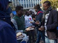 Раздача еды в лагере мигрантов в районе Сталинград в Париже