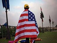 Индийский рабочий с американским флагом в Нью-Дели накануне приезда президента США Барака Обамы