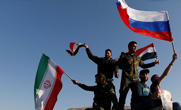 Сирийцы размахивают иранскими, российскими и сирийскими флагами, протестуя против воздушных ударов коалиции под командованием США в Дамаске, 14 апреля 2018