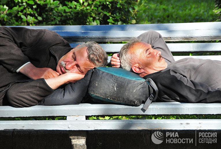 Мужчины спят на скамейке на Тверском бульваре в Москве