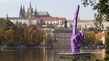 Скульптура в виде фрагмента руки с вытянутым вверх 10-метровым средним пальцем на понтоне на реке Влтава напротив Пражского Града