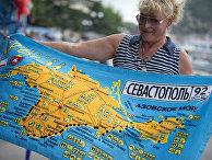 Женщина рассматривает пляжное полотенце с картой Крыма