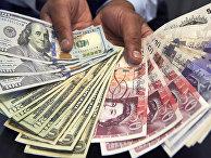 Доллары США и британские фунты стерлингов в одном из магазинов в Лондоне