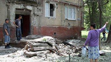 Жители во дворе жилого дома, пострадавшего в результате обстрела, в поселке Горловка Донецкой области