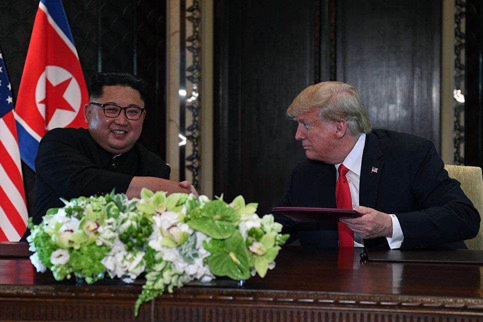 Лидер КНДР Ким Чен Ын и президент США Дональд Трамп во время церемонии подписания документов по итогам встречи в Сингапуре. 12 июня 2018