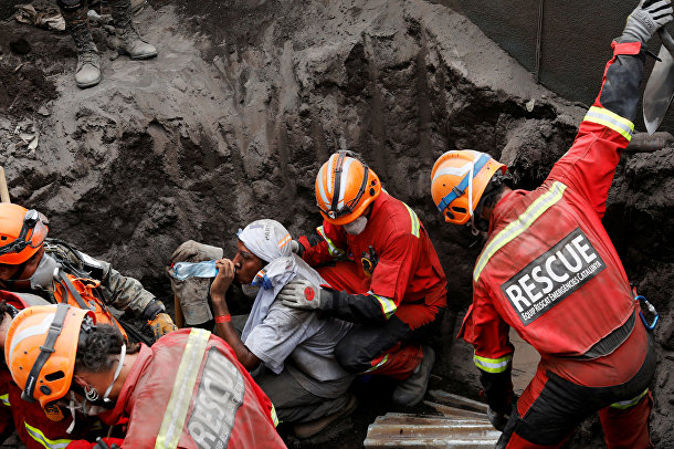 Спасатели во время поиска пострадавших от извержения вулкана Фуэго в Гватемале