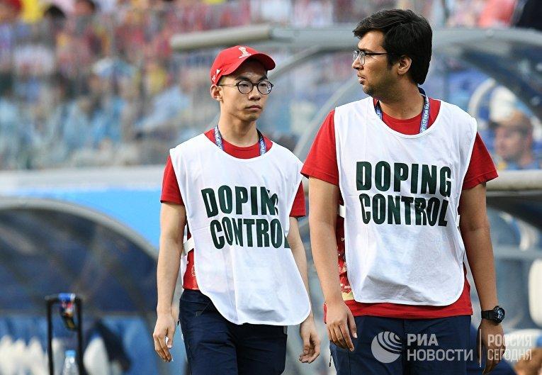 Сотрудники допинг-контроля на поле стадиона