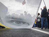 Митингующие держат плакат с изображением Олега Сенцова во время митинга оппозиции в Москве
