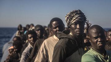 Беженцы из разных африканских стран на борту переполненного резинового катера в Ливии