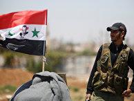 Солдат сирийской армии с флагом Сирии недалеко от Деръа
