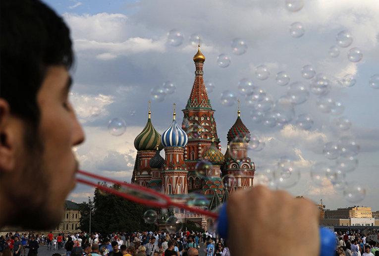 Молодой человек пускает мыльные пузыри на Красной площади в Москве