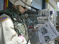 Капитан армии США Пирс Томас читает газету в Багдаде, Ирак