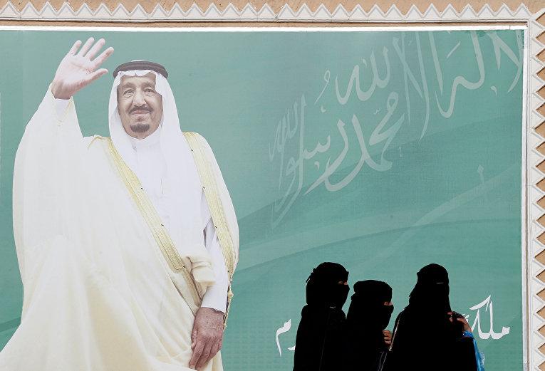Женщины идут мимо плаката Короля Саудовской Аравии Салмана бин Абдулазиз Аль Сауда в Эр-Рияде