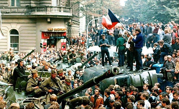 Жители Праги с чешскими флагами перед советскими танками
