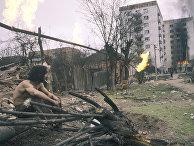 Житель Грозного смотрит на горящие дома