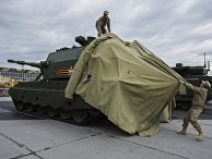 Сотрудники снимают тент с 152-миллиметровой самоходной артиллерийской установки «Коалиция-СВ»