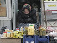 Пожилая женщина торгует на улице в Киеве