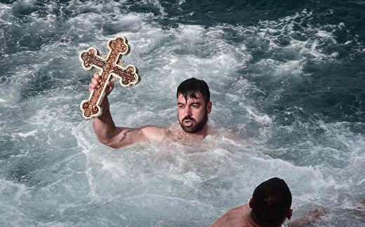 Мужчина во время обряда, посвященного православному Богоявлению близ Афин