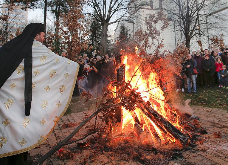 Священник сжигает ветви дуба у храма Святого Саввы в Белграде