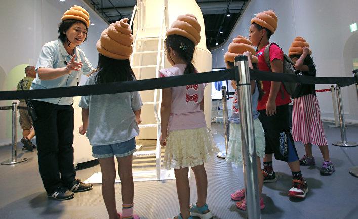 Экскурсовод в Национальном музее развития науки и инноваций в Токио рассказывает детям в шапочках в виде какашек о работе канализации