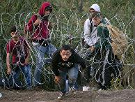 Мигранты пролезают под забором из колючей проволоки и попадают на территорию Венгрии