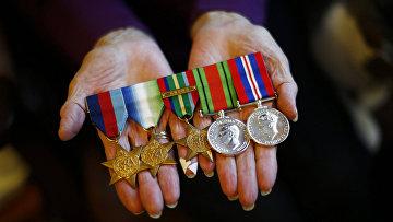 Мэри Барбер показывает медали своего мужа, ветерана Второй мировой войны