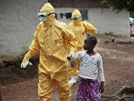 Девятилетнюю Нову Пайе забирают сотрудники службы скорой помощи после появления признаков лихорадки в деревне Фримэн Резерв