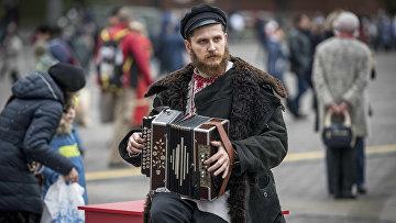 Музыкант играет на аккордеоне на Манежной площади в центре Москвы