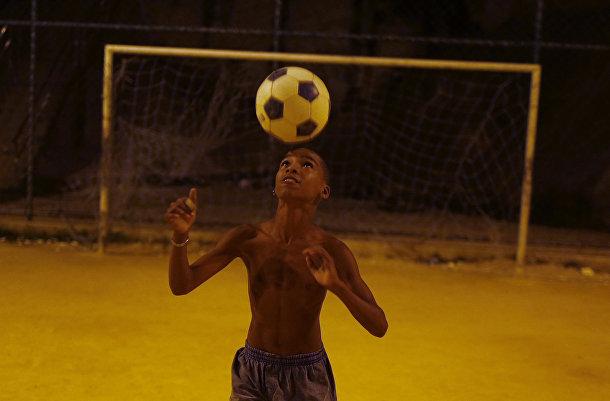 Мальчик играет в футбол в трущобах Сао-Карлос в Рио-де-Жанейро