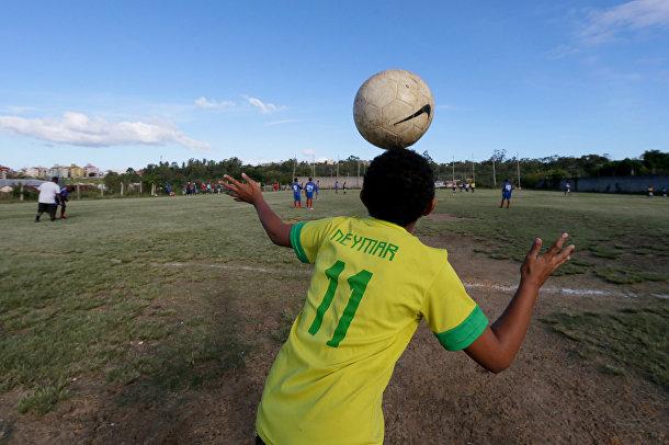 Мальчик в футболке с именем нападающего сборной Бразилии Неймара наблюдает за матчем-пеладой в окрестностях Порту-Алегри