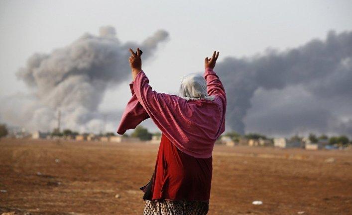 Женщина смотрит на то, как над Кобани поднимается дым после американского авиаудара