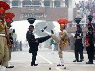 Пакистанские рейнджеры и бойцы войск пограничной безопасности Индии во время ежедневной церемонии спуска флагов в Вагахе