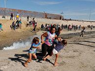 Мигранты из Гондураса бегут от слезоточивого газа, распыленного американскими пограничниками. 26 ноября 2018