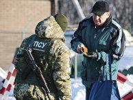 Украинский пограничник проверяет документы на границе с РФ в Гоптовке