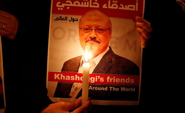 Демонстрант держит плакат с изображением саудовского журналиста Джамала Хашогги