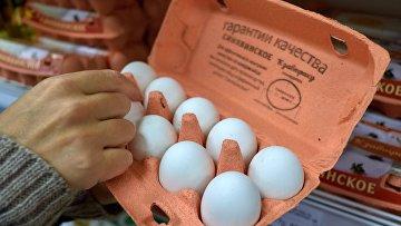 Покупатель выбирает куриные яйца вмагазине «Полушка» вСанкт-Петербурге