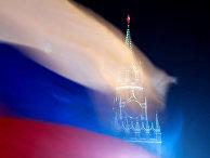 Российский флаг на фоне Спасской башни Московского Кремля в Москве