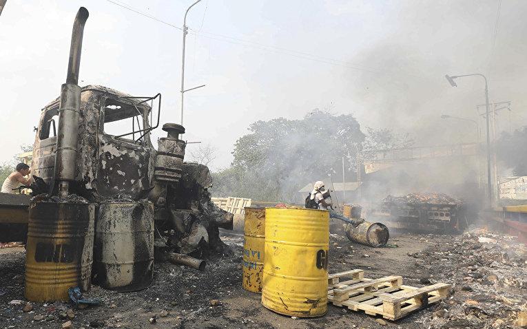 Обугленные грузовики, бывшие частью гуманитарной помощи, направляющейся в Венесуэлу в Кукуте