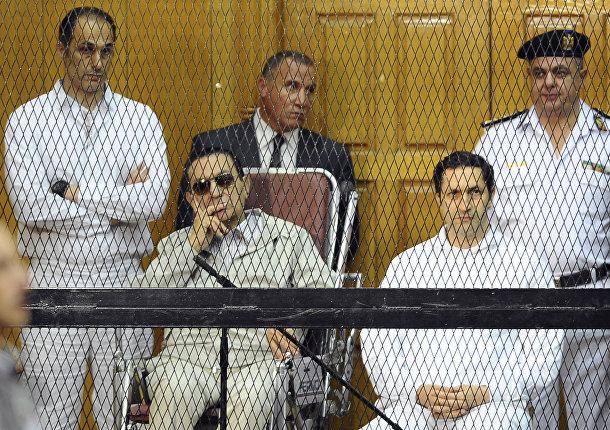 Бывший президент Египта Хосни Мубарак (сидящий в центре слева) и его сыновья Гамаль Мубарак (слева) и Алаа Мубарак (справа)