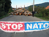 Плакат и заблокированная дорога в знак протеста против НАТО в деревне Зупце на севере Косово