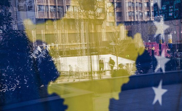Прохожие в Приштине через окно, украшенное флагом Косова