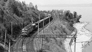Поезд едет по берегу озера Байкал